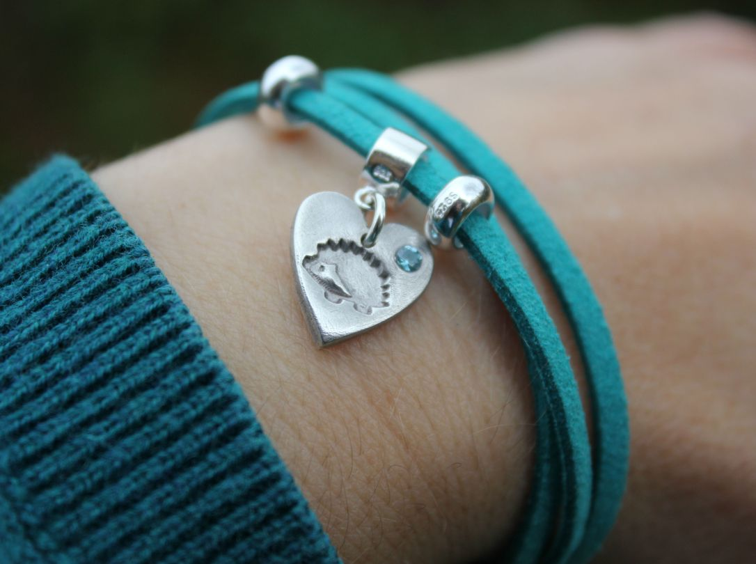 Teal hedgehog bracelet with blue zircon gemstone on wrist.JPG
