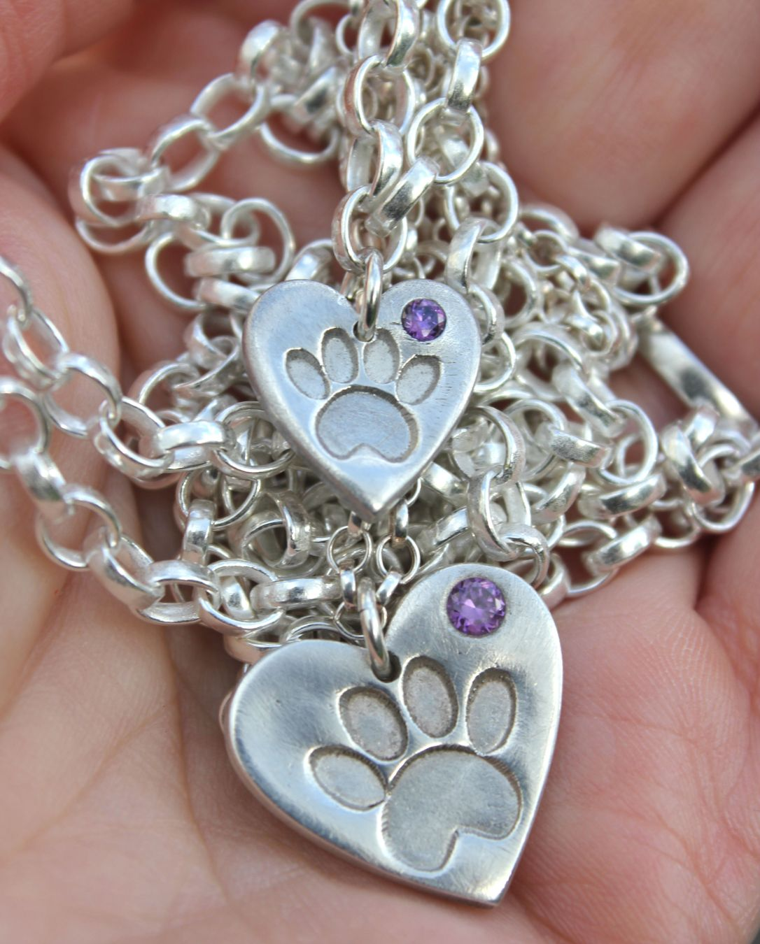 Large and small birthstone paw print pendants in hand.JPG