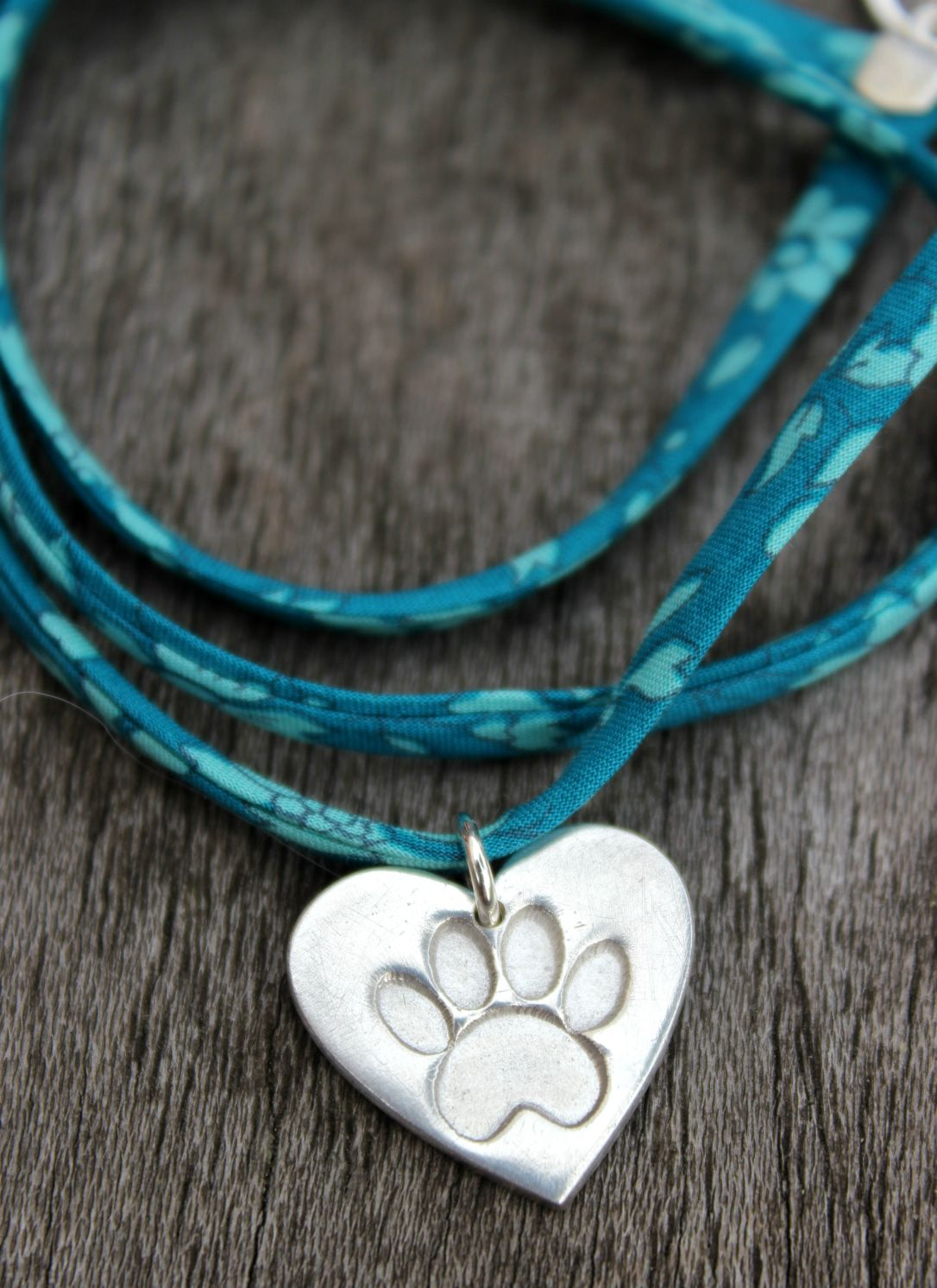 paw print liberty bracelet on teal ribbon